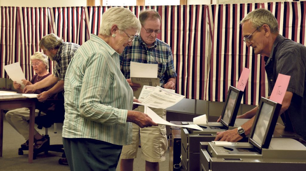 "Election clerk Richard Irwin watches as Shirley Boone casts one of three ballots for local and state elections in Skowhegan on Tuesday. Town clerk Gail Pelotte commented on voter turnout by noon time saying, ""It's been crazy busy so far today."""