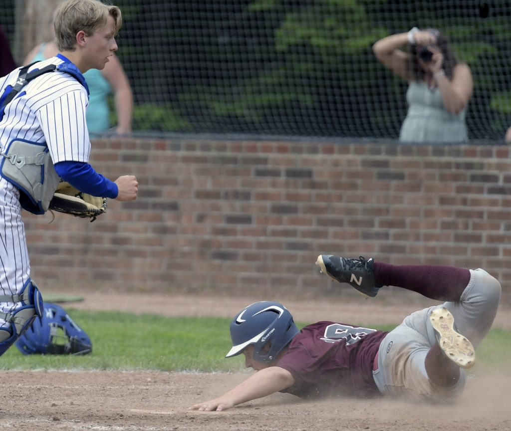 Richmond's Kyle Tilton slides into home in front of Searsport's Charlie Spiegel during a Class D South regional final game Wednesday in Standish.