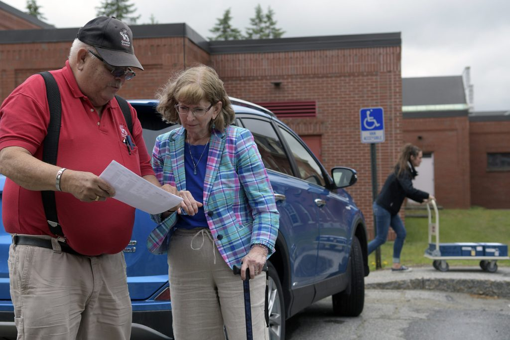 Deputy Secretary of State Julie Flynn confers with General Courier deliveryman Daniel Young on Thursday after he arrived in Augusta with ballots in preparation for the state's first ranked-choice voting tabulation process, which is scheduled to begin today. The ballots, at right, were carted into a state office building.