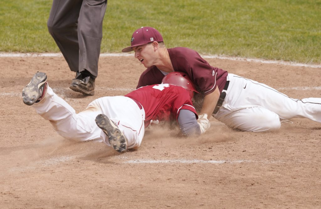 Bangor baserunner Zach Murray slides head first into home and into the chest of Gorham's Jacob Sladen during the Class A baseball final Saturday at St. Joseph's College in Standish. Murray was safe on the play.