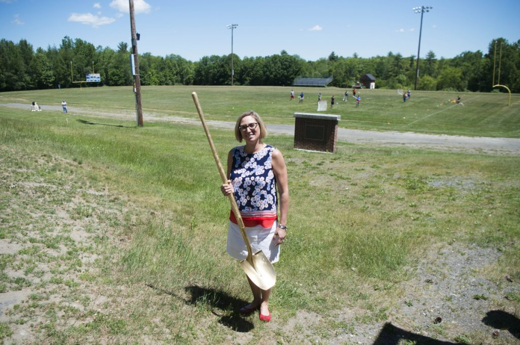 Lisa Burton, president of the Messalonskee All Sports Boosters and a leader of the effort to replace Messalonskee High School's outmoded track and football field, behind her, with an eight-lane track and an all sports turf field, stands ready with a ceremonial gold shovel Friday for the groundbreaking at the complex.