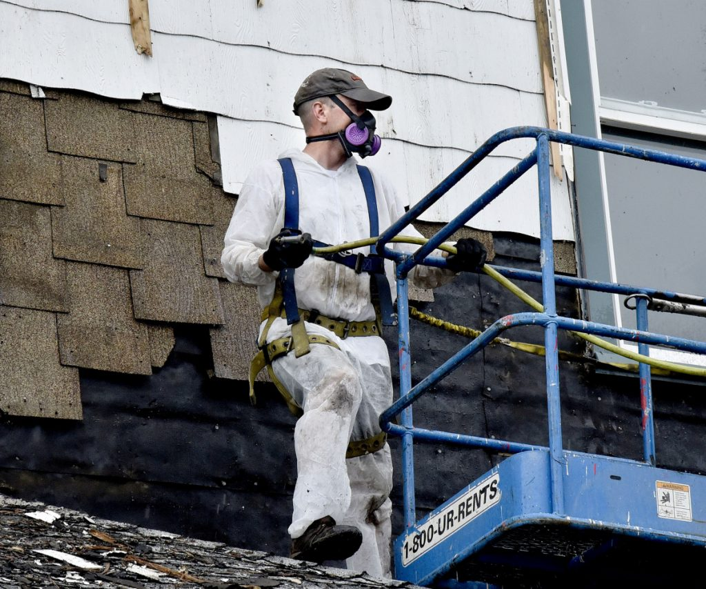 Eben Henderson wears a respirator while tearing off siding on the historic Kennebec Valley Inn in Skowhegan on Monday.