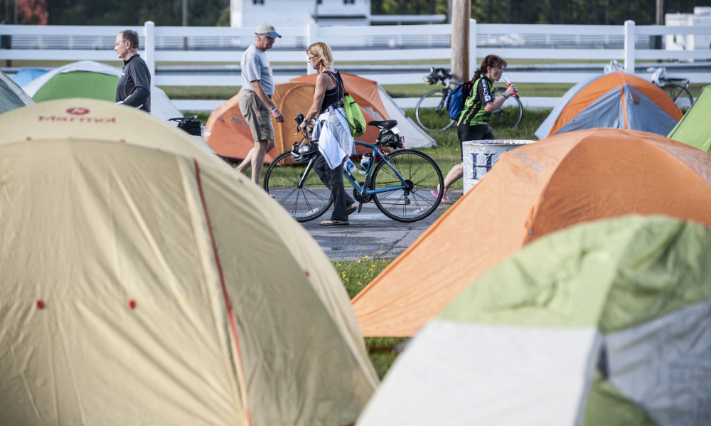 Cyclists walk to their tents in September at the Skowhegan Fairgrounds on the night before the start of the annual BikeMaine cycling trek.