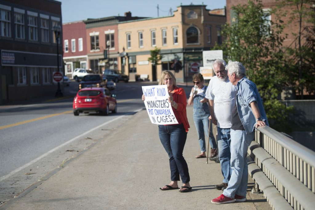 Hope Savage holds a sign Wednesday on the Margaret Chase Smith Bridges in Skowhegan in protest of the detention and separation of immigrant families along the Mexican border.