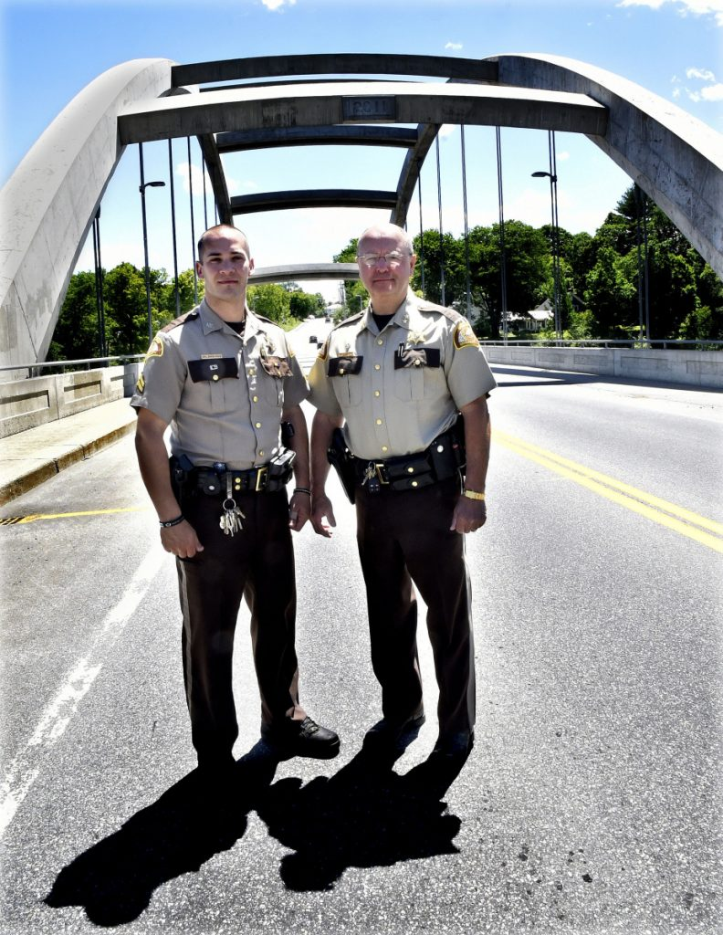 Somerset Deputy David Cole, left, son of Cpl. Eugene Cole, who was killed in the line of duty, and Somerset Sheriff Dale Lancaster on Thursday stand on the bridge spanning the Kennebec River in Norridgewock that a bill in the Legislature calls for naming the Cpl. Eugene Cole Memorial Bridge.