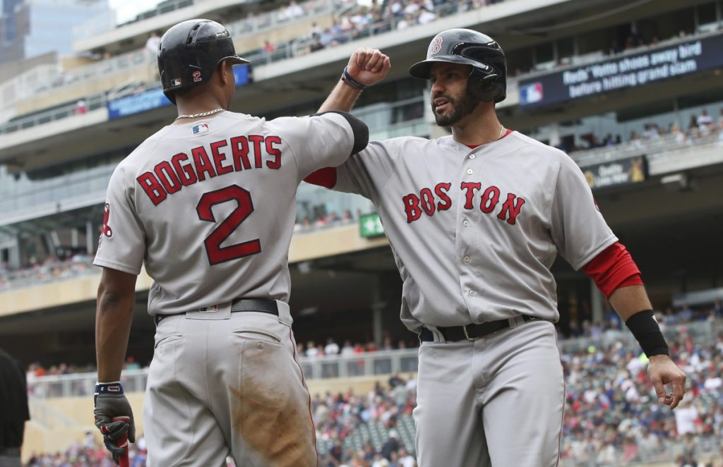 Boston's Xander Bogaerts, left, celebrates with J.D. Martinez after he scored on a double by Mitch Moreland in the eighth inning Thursday in Minneapolis. The Red Sox won 9-2.