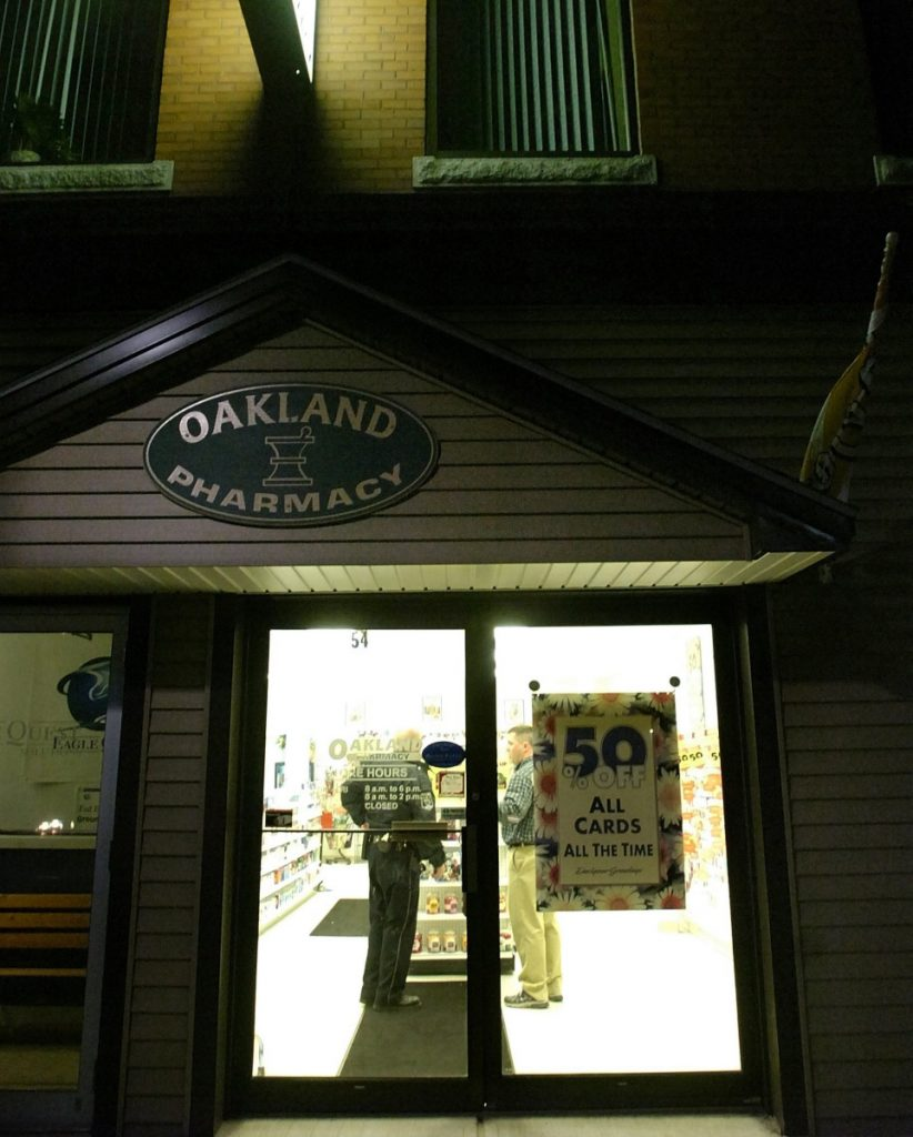 A police officer talks to a person inside The Oakland Pharmacy on Main Street as part of the investigation of a robbery that occurred there on Oct. 31, 2007.