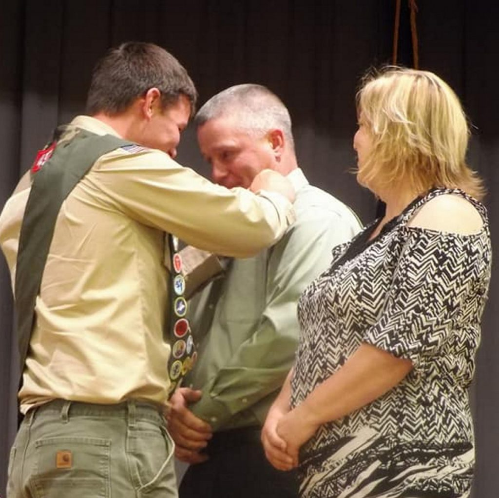 Hunter Cuddy presents a pin to his father Ed Cuddy for all of his support during Hunter's Scouting career, as his mom Michele Cuddy looks on.