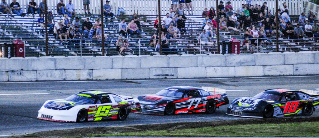 Staff photo by Joe Phelan Nick Hinkley (15) leads Nick Reno (77) and Kevin Douglass (18) during a Pro Stock feature Saturday night at Wiscasset Speedway. Hinkley won his third race of the season.