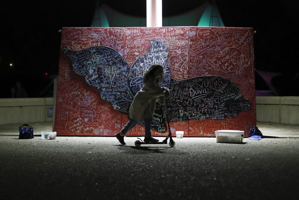 A child plays beside a message board adorned with notes for loved ones who took their own lives during an Out of the Darkness Walk event  on Oct. 15, 2017, organized by the Cincinnati Chapter of the American Foundation for Suicide Prevention at Sawyer Point Park in Cincinnati. Suicide rates inched up in nearly every U.S. state from 1999 through 2016, according to a new government report released Thursday.
