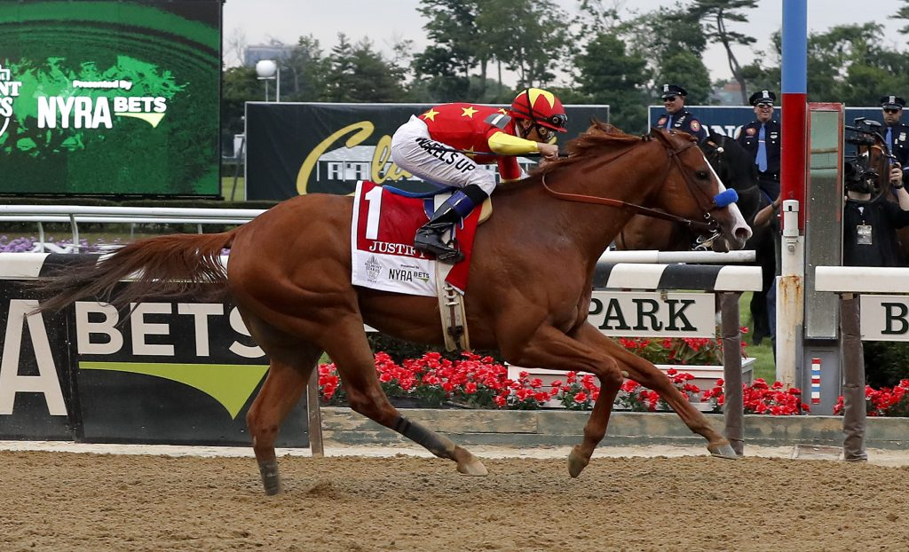 Justify (1), with jockey Mike Smith up, crosses the finish line to win the 150th running of the Belmont Stakes on Saturday in Elmont, N.Y. Justify became the 13th horse to win the Triple Crown.