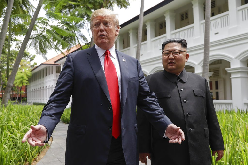 President Trump and North Korea leader Kim Jong Un stop to talk with the media as they walk from their lunch at the Capella resort on Sentosa Island, Singapore.