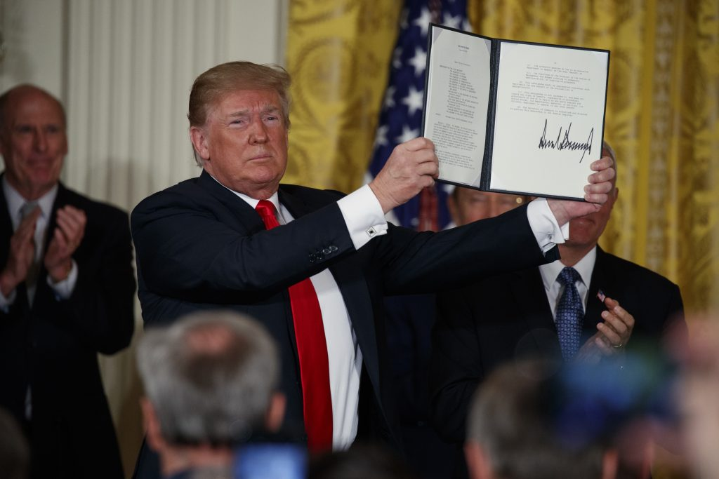 """President Donald Trump shows off a """"Space Policy Directive"""" after signing it Monday during a meeting of the National Space Council in the East Room of the White House."""