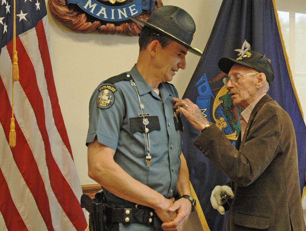Morris Cote, of Houlton, pins the badge on his son, John Cote, of China, at John Cote's swearing in as the chief of the Maine State Police on Monday in Augusta.