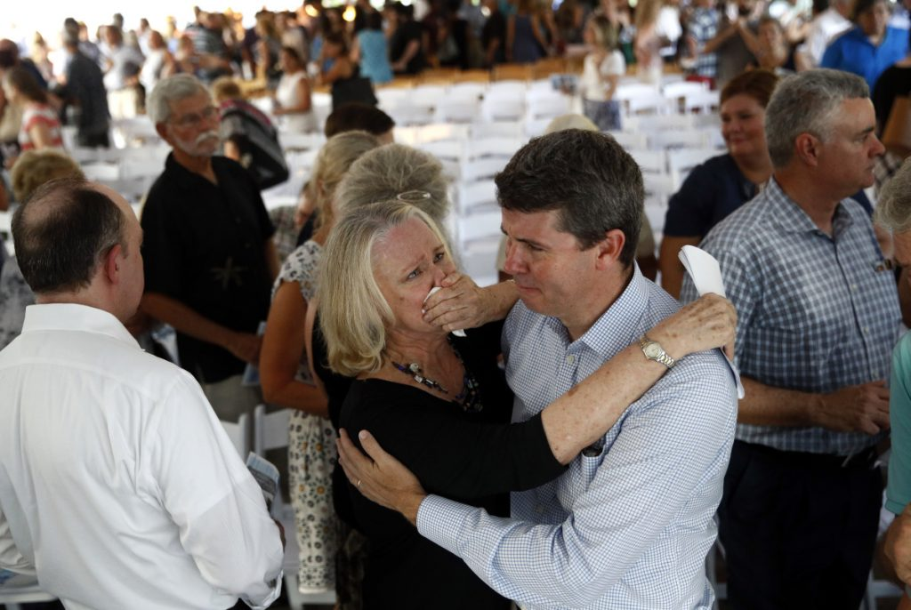 Judy Hiaasen, center left, sister of Rob Hiaasen, one of the journalists killed in the shooting at The Capital Gazette newspaper offices, hugs her nephew Scott following a memorial service Monday in Owings Mills, Md. ()