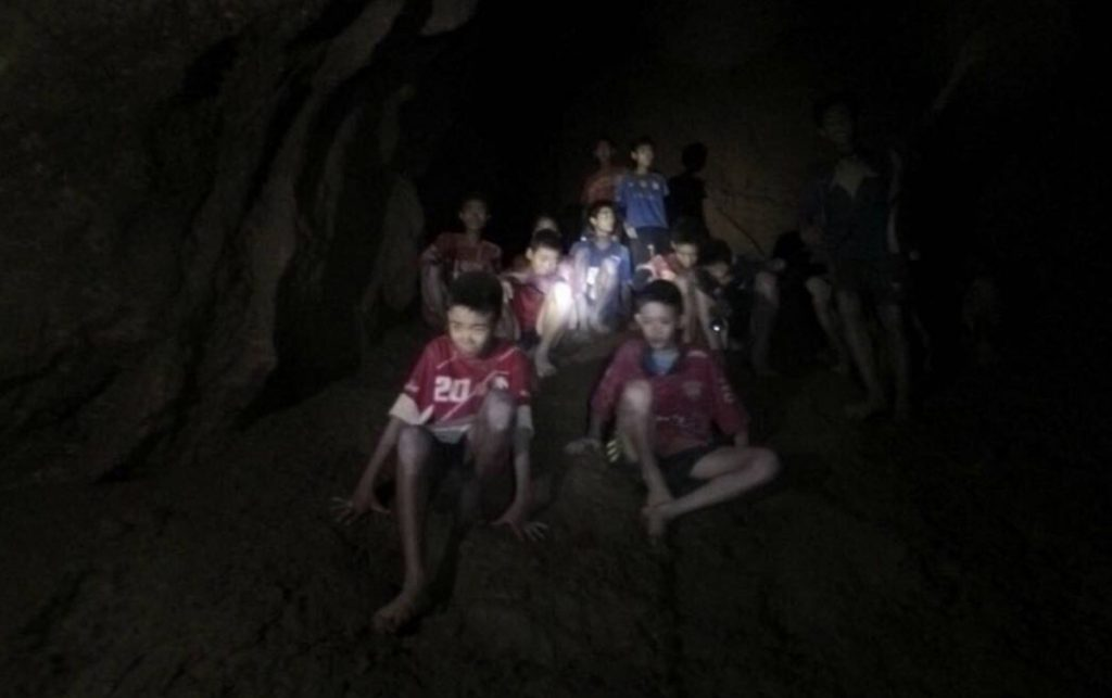 The boys and their soccer coach are shown as they were found Monday by rescuers, keeping dry in a partially flooded cave in Mae Sai, Chiang Rai, Thailand. After being trapped for 10 days, they were mostly in stable medical condition and have received high-protein liquid food, officials said Tuesday.
