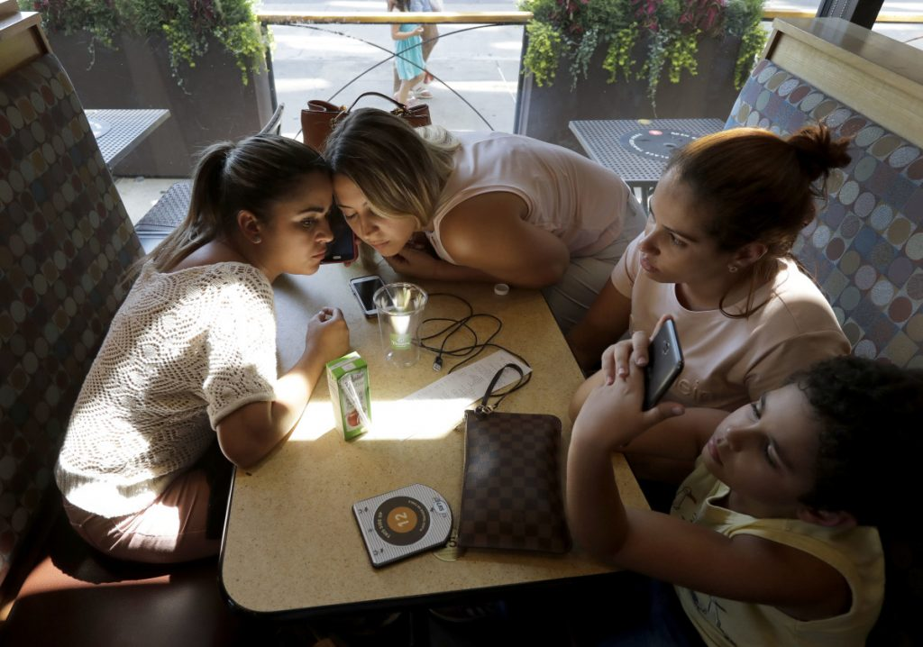 Sirley Silveira Paixao, an immigrant from Brazil seeking asylum, left, and paralegal and interpreter Luana Mason listen on the phone to Denise Brown, director of Heartland Human Care Service, on the procedures Paixao needs to fulfill to get her son Diego released from immigration detention in Chicago, on Friday. Seated with them are Lidia Karine Souza, second from right, and her son Diogo, who recently was released from immigration detention. Paixao and her son arrived in this country from Brazil on May 22, and were separated shortly after. She was released on June 13 and has been living in Massachusetts, while her son was taken to Chicago.