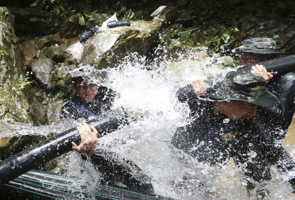 Thai soldiers try to connect water pipes aimed at keeping water from getting back inside a cave in northern Thailand where 12 boys and their soccer coach have been trapped since June 23. A letter containing notes from trapped team members and retrieved by divers, was made public Saturday.