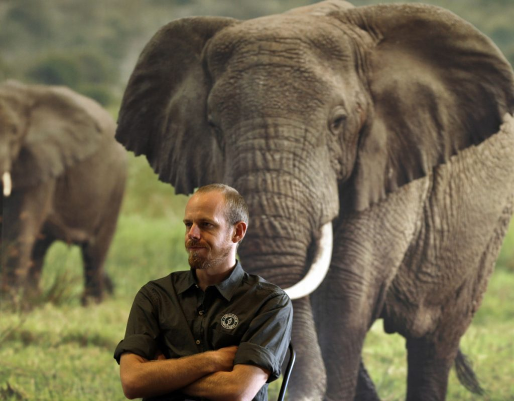 Erik Mararv, manager of the Garamba National Park in Congo, is shown against a poster of elephants during a 2016 interview.