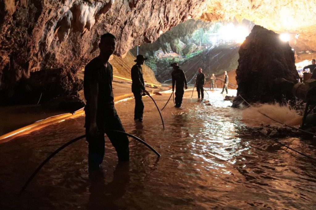 Rescue teams arrange a water pumping system at the entrance of a flooded cave, where 12 boys and their soccer coach had been trapped since June 23, in Mae Sai, Chiang Rai province, northern Thailand. Expert divers extracted four boys on Sunday.
