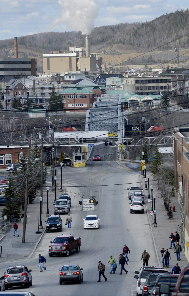 MADAWASKA, ME - MAY 8: Paper Mill workers file out onto Bridge Ave. after their shift Thursday, May 8, 2014.  Edmundston, Canada can be seen across the bridge.(Photo by Shawn Patrick Ouellette/Staff Photographer)