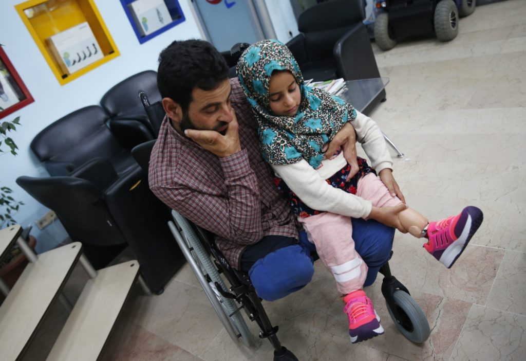 Maya Meri adjusts her prosthetic leg as she sits on her father Mohammed's lap at a rehabilitation clinic in Istanbul. Maya, an 8-year-old girl from war-torn Syria who was born without legs, has been in the spotlight since images of her plight hit social media last month. Her father had made substitute legs for her from tuna cans, plastic tubes and fabric.