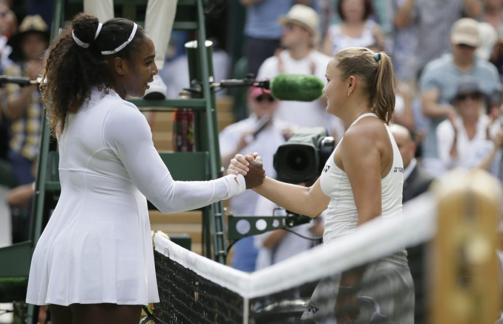 Serena Williams, left, shakes hands with Russia's Evgeniya Rodina after defeating her in straight sets Monday at the Wimbledon tennis championships in London. (AP Photo/Tim Ireland)