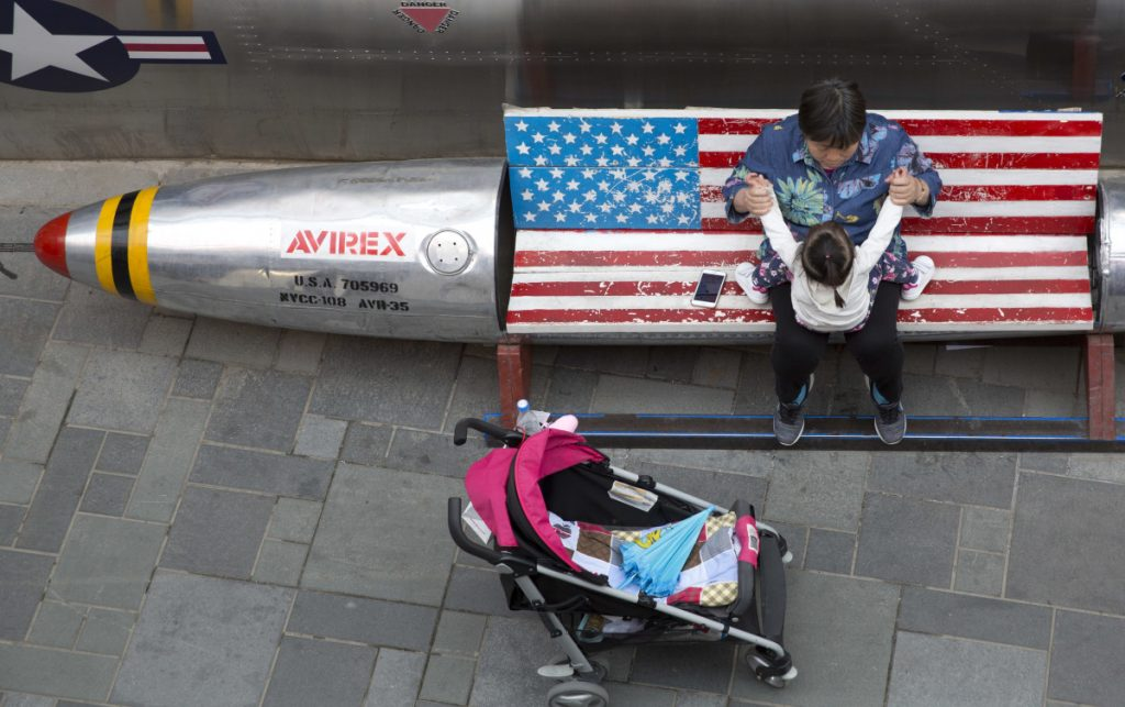 A woman tends to a child near a promotional gimmick in the form of a bomb and the American flag outside a U.S. apparel shop in Beijing. One of China's options in a trade war is to make operating difficult for U.S. companies there.