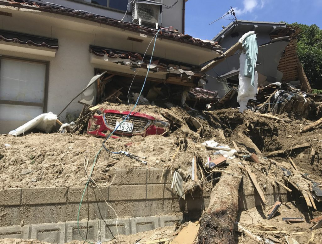 A car is covered with mud as houses are damaged after a mudslide caused by heavy rains in Hiroshima.