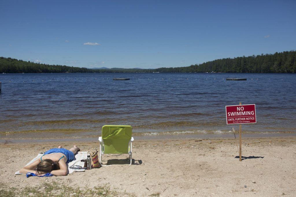 Christy Dow of Naples tans Saturday on Woods Pond Beach in Bridgton, next to one of the no-swimming signs that lined the sand. Swimming at the popular beach was banned when several people fell ill after being in the water, but officials reopened the swimming area Tuesday because tests showed the water is safe.