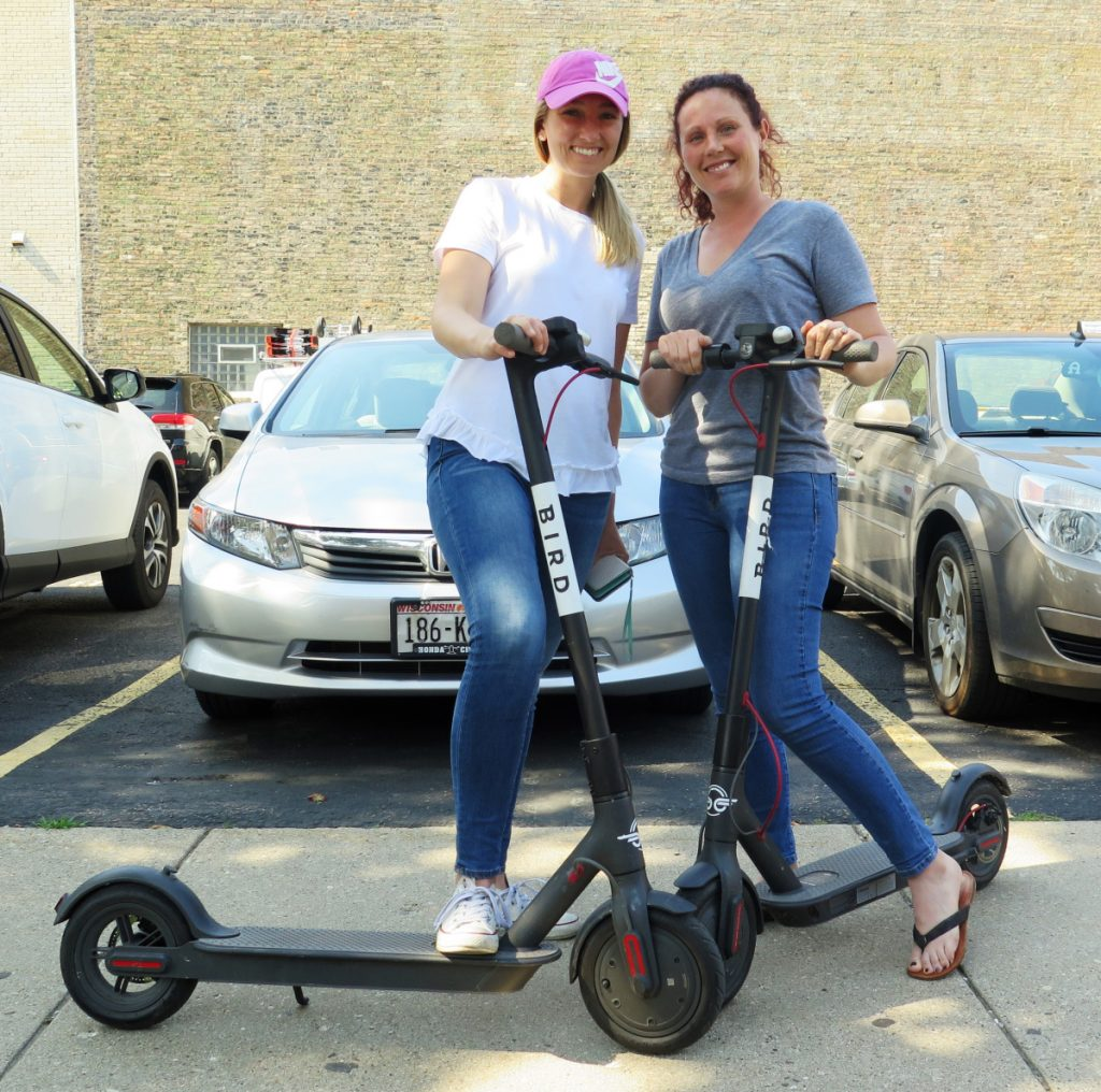 Kirby Bridges, left, and Megan Garlington pose with the Bird scooters they were taking for a ride in Milwaukee. Milwaukee is suing California-based Bird to stop the company from renting bikes because the city contends they are illegal to operate on streets and sidewalks.