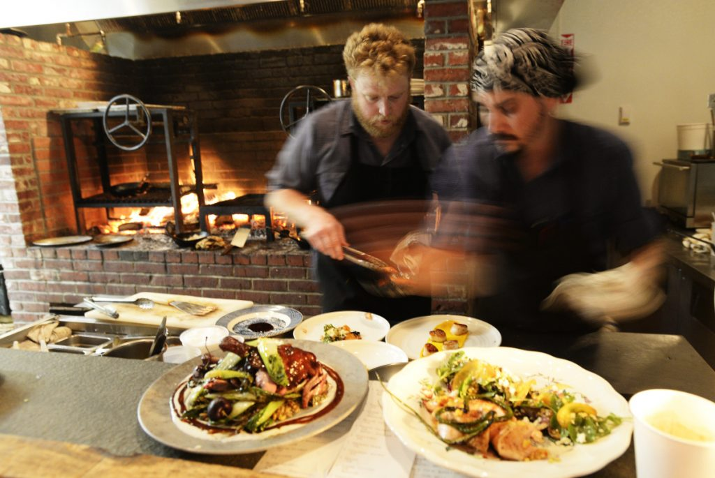 Cooks Matt Jauck, left, and Sean Kach prepare plates in the Walkers Maine kitchen. Chef/owner Justin Walker said the fireplace hearth burns through a cord of wood per week.