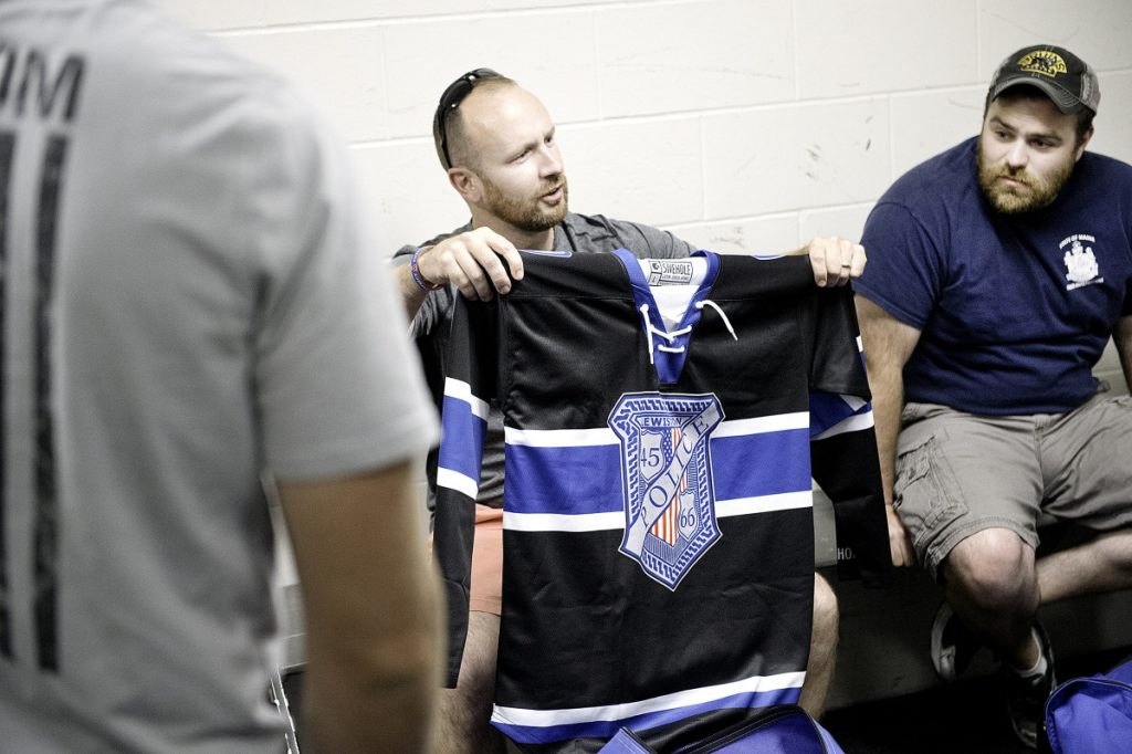 Lewiston police Officers Charlie Weaver, left, and Tyler Michaud look at the new hockey jerseys that the Lewiston Police Department hockey team wore during the game.