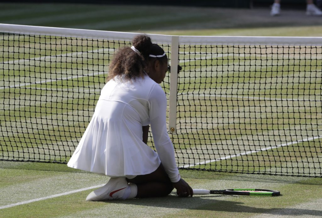 Serena Williams kneels at the net after missing a volley during the second set of her loss to Germany's Angelique Kerber at the Wimbledon Tennis Championships in London on Saturday.