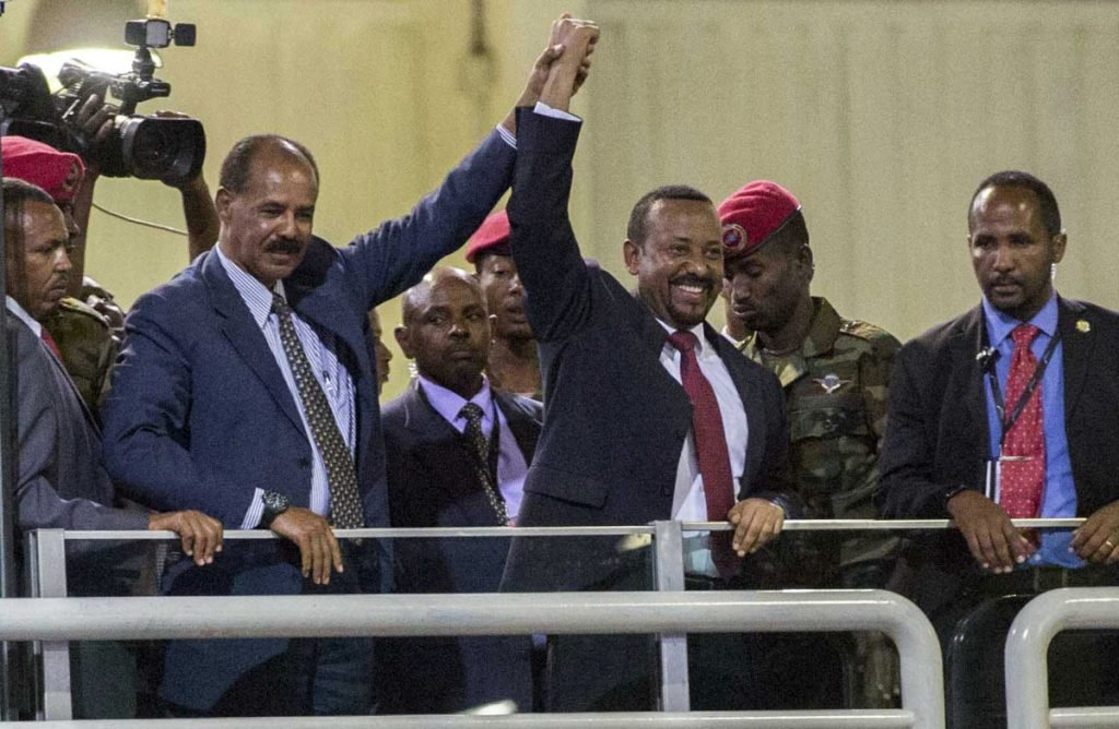 Eritrean President Isaias Afwerki, second left, and Ethiopia's Prime Minister Abiy Ahmed, center, hold hands as they wave at the crowds in Addis Ababa, Ethiopia, on Sunday.