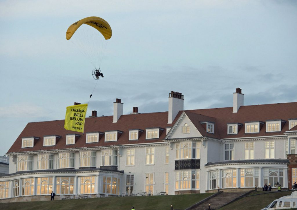 "A Greenpeace protester flies a microlight over President Trump's resort in Turnberry, South Ayrshire, Scotland, with a banner reading ""Trump: Well Below Par."""