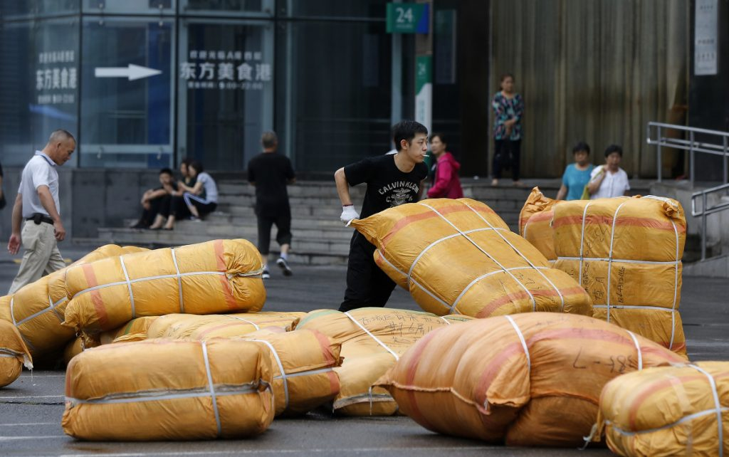 A worker loads goods outside a retail and wholesale clothing mall in Beijing. China's filing of a complaint with the WTO may help rally support from governments critical of U.S. actions to impose tariffs on Chinese and other imports.