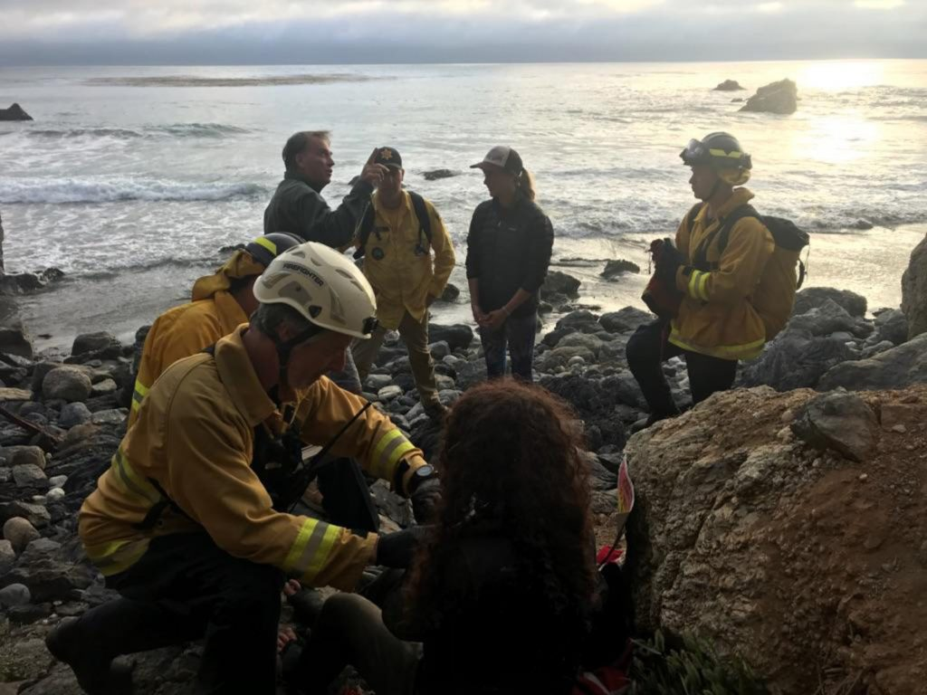 """Authorities tend to Angela Hernandez, foreground center, as she is rescued from an isolated beach in Morro Bay, Calif. """"For her to survive for seven days ... with injuries that she had is amazing,"""" the sheriff said."""