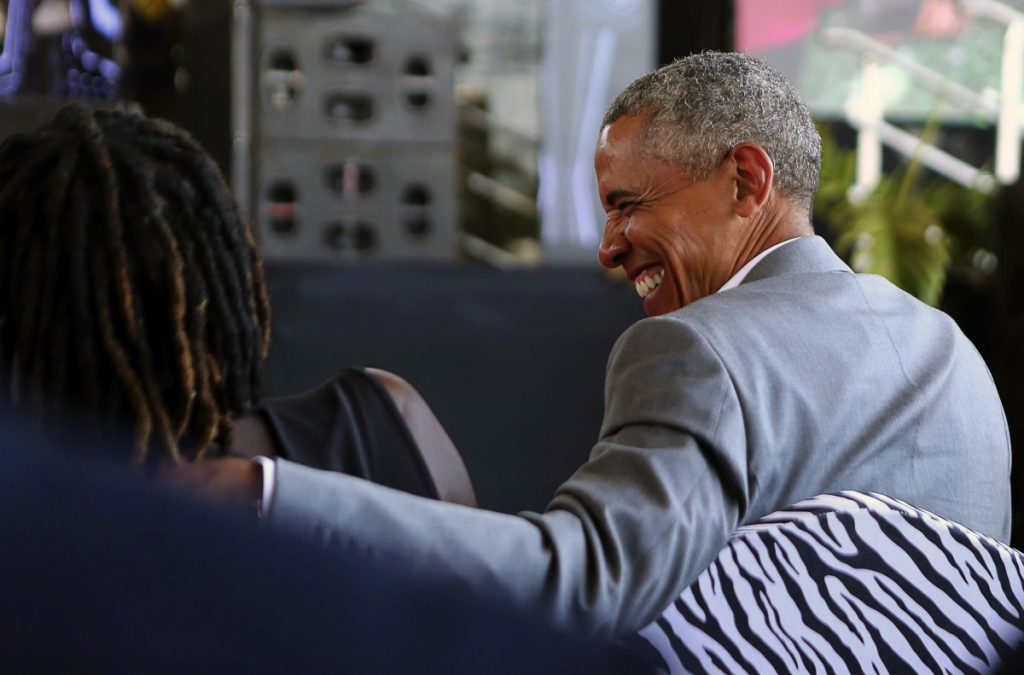 Former President Obama speaks with his half sister Auma Obama, in Kogelo, Kenya on Monday. Obama on Monday praised Kenya's president and opposition leader for working together but said this East African country must do more to end corruption. The former president is scheduled to give his highest profile address since leaving office to mark the 100th anniversary of Nelson Mandela's birth.