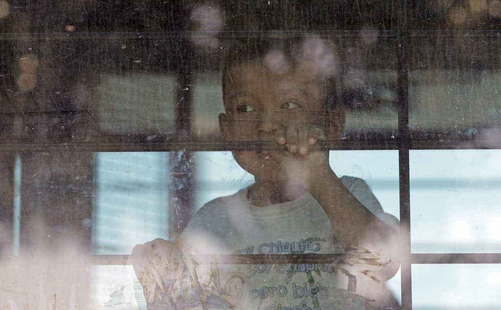 An immigrant child looks out from a U.S. Border Patrol bus leaving as protesters block the street outside the U.S. Border Patrol Central Processing Center in McAllen, Texas, last month. Immigrant children described hunger, cold and fear in a voluminous court filing about the facilities where they were held in the days after crossing the border.