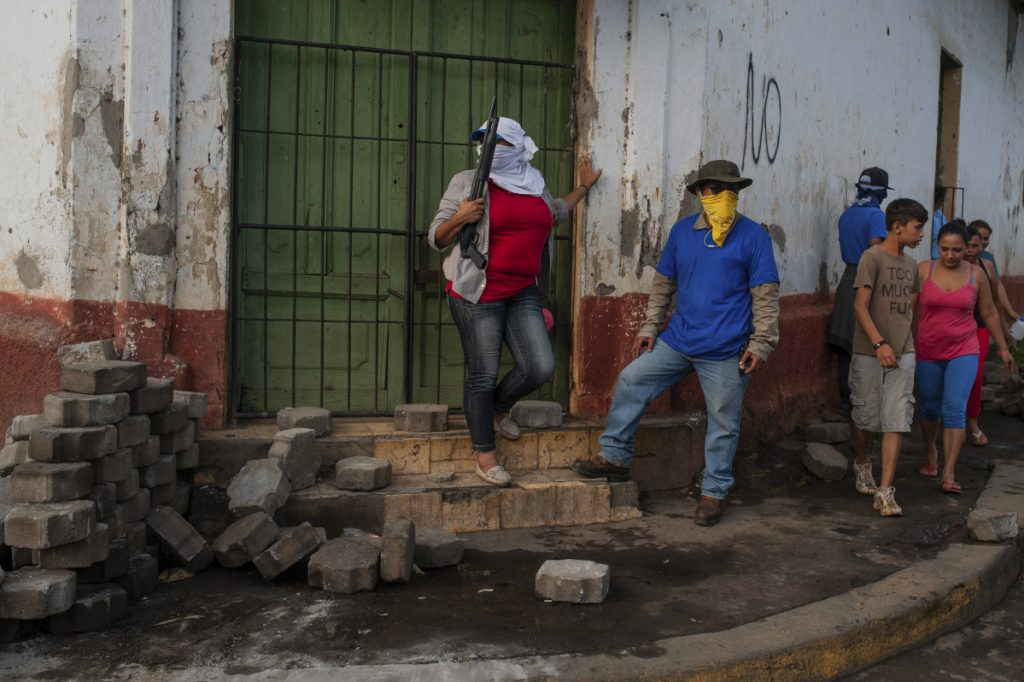 Sandinista militias stand guard at a torn down barricade after police and pro-government militias stormed the Monimbo neighborhood of Masaya, Nicaragua on Tuesday.