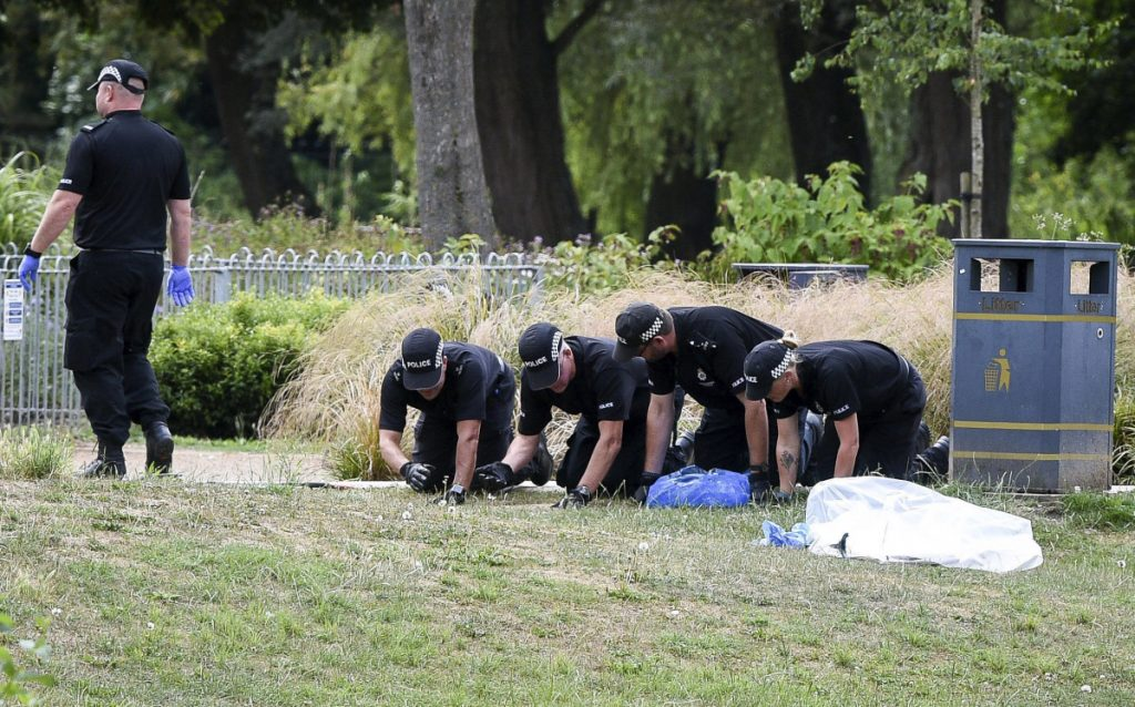 Police conduct fingertip searches of Queen Elizabeth Gardens in Salisbury, which British woman Dawn Sturgess visited before she fell ill after being exposed to nerve agent Novichok. Senior coroner David Ridley opened an inquest into the poisoning death of Sturgess on Thursday, but said the cause of death won't be given until further tests are completed. (Ben Birchall/PA via AP)