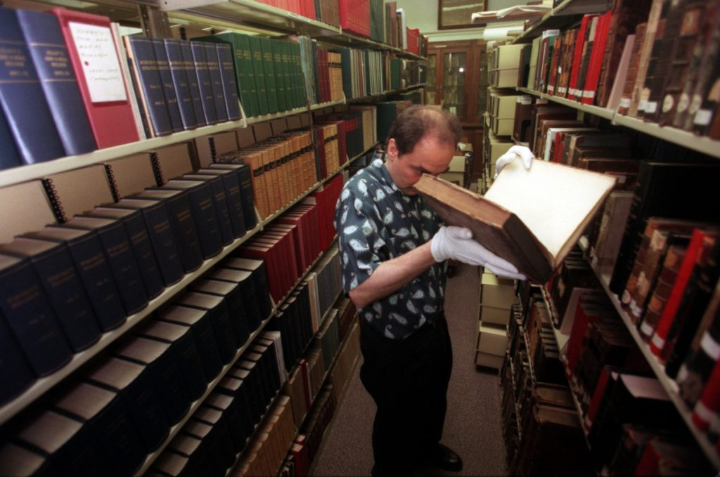 Greg Priore, an archivist at the Carnegie Library of Pittsburgh, examines books for preservation. Sammy Dallal/Pittsburgh Post-Gazette via AP