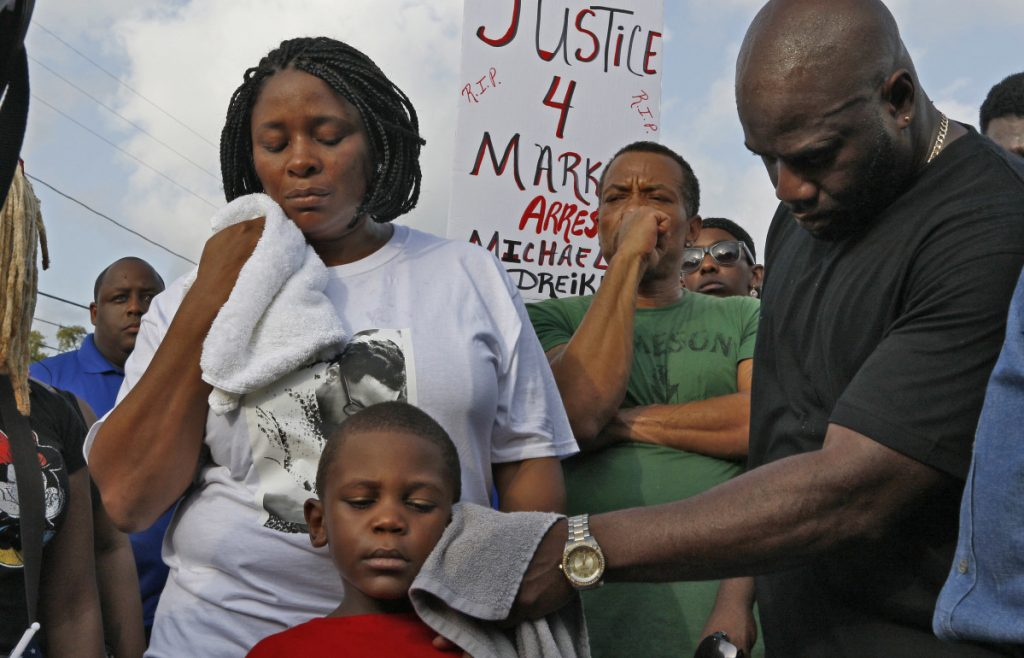 Michael McGlockton, right, the father of Markeis McGlockton, wipes the face of his grandson, Markeis McGlockton Jr., as protesters gathered Sunday in Clearwater Fla.