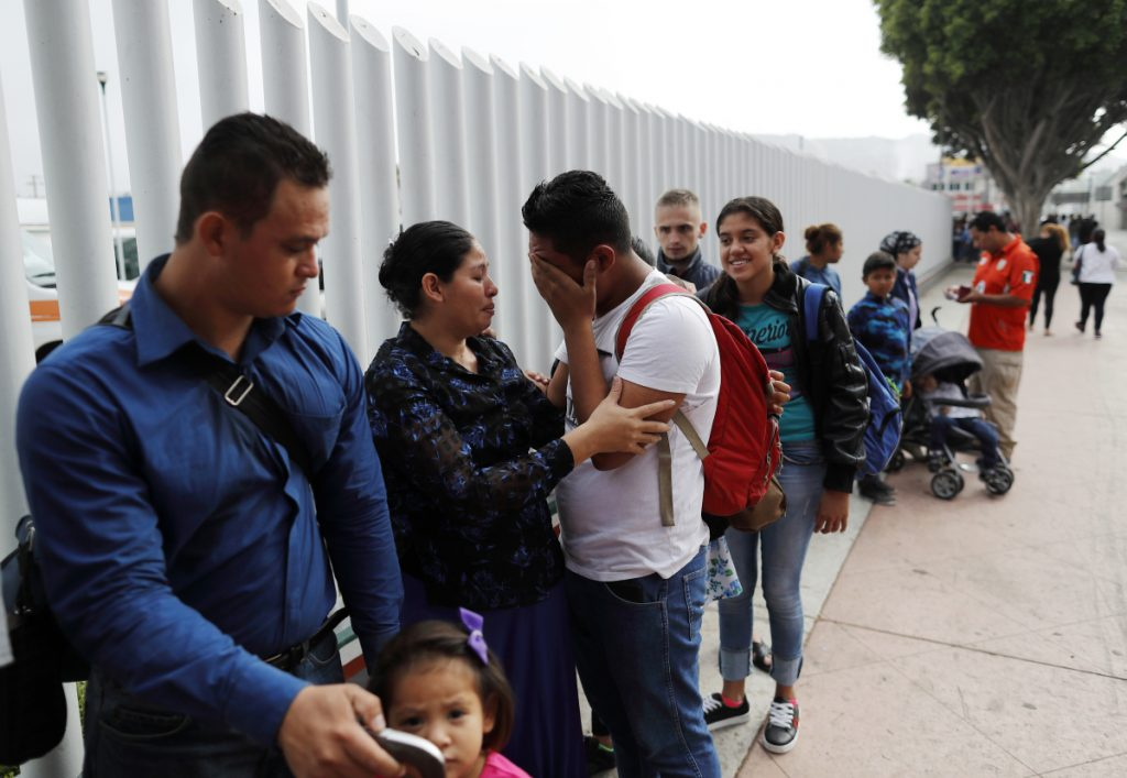 Calet Garcia, center, of Honduras, cries once he realizes he will be able to apply for asylum in the U.S. with his friend Daisy Avelar, second from left, of El Salvador, on Thursday near the San Ysidro port of entry in Tijuana, Mexico.