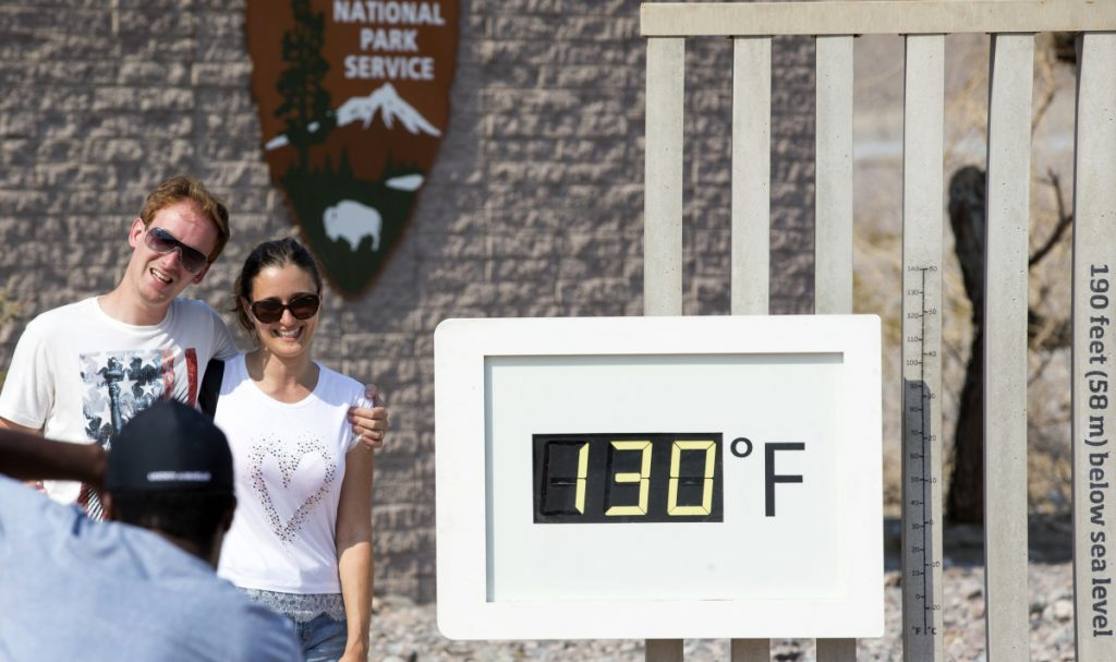 A couple poses at the Furnace Creek Visitor Center thermometer in Death Valley National Park, Calif., one of many areas experiencing record or near-record heat.