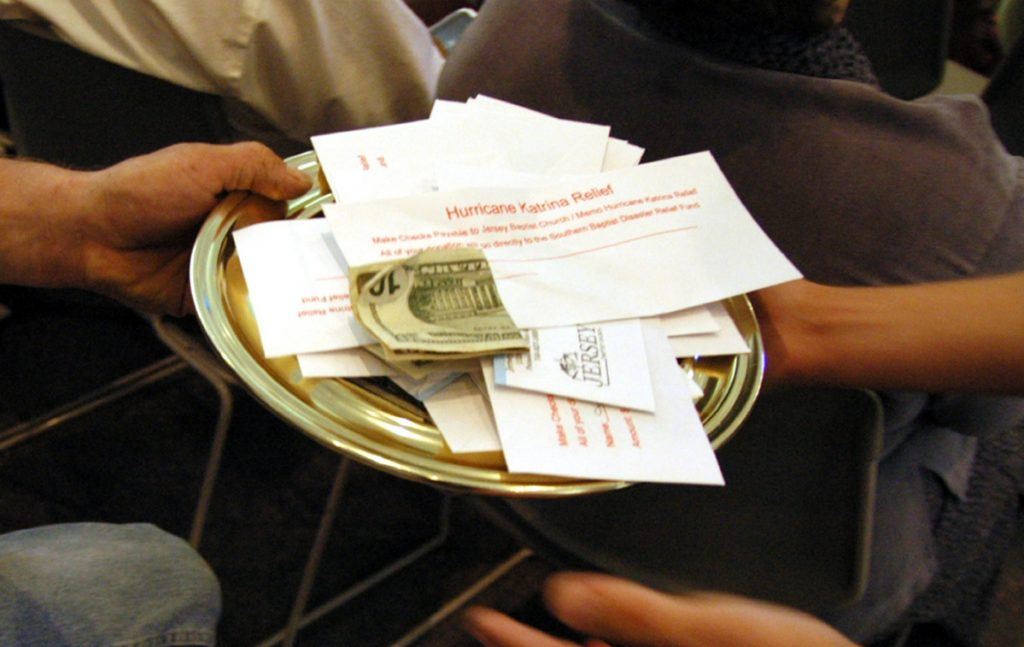 A collection plate containing envelopes specifically for the victims of Hurricane Katrina is passed during church service, at the Jersey Baptist Church in Pataskala, Ohio, in 2005.