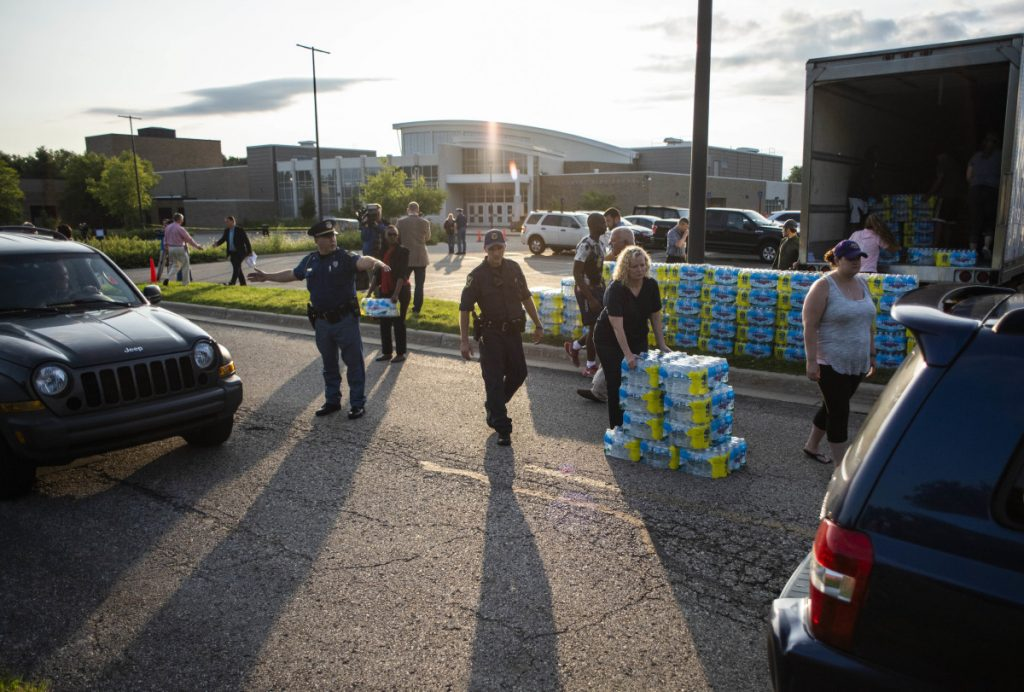 Emergency response teams hand out free bottled water to residents at the Parchment High School in Parchment, Mich., on Friday.