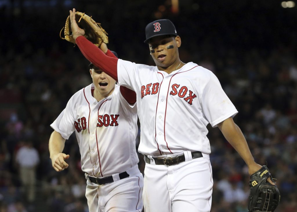 Boston Red Sox third baseman Rafael Devers, right, was placed on the disabled list before Sunday's series finale with a strained left hamstring.