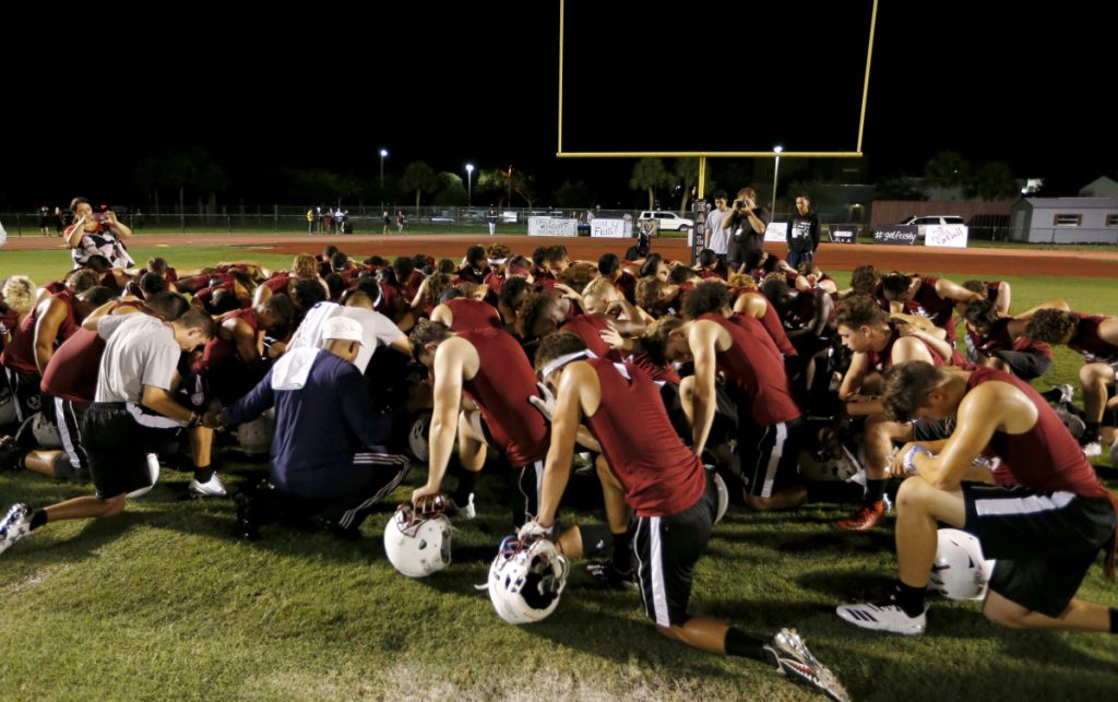 Members of the Marjory Stoneman Douglas High School football team pray together as they began practice for a new season just after midnight on Monday. Below, a coach wears a logo honoring the 17 lives lost in the February shooting.